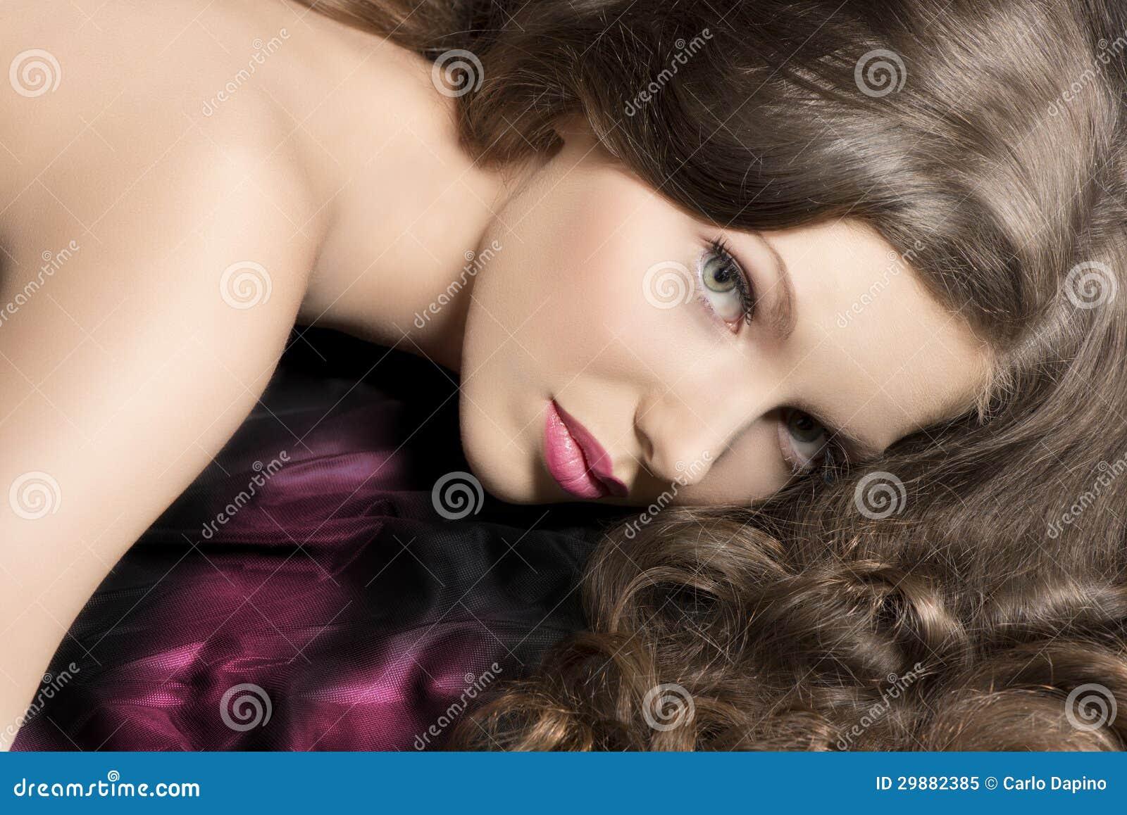 Portrait de beauté de fille menteuse avec le visage sur le tissu foncé