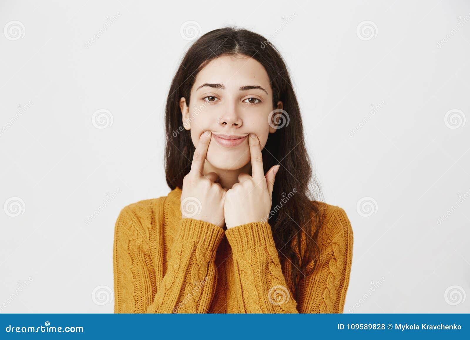 Portrait en gros plan de la fille percée caucasienne fatiguée et sombre étirant la bouche avec des doigts, faisant le faux sourir