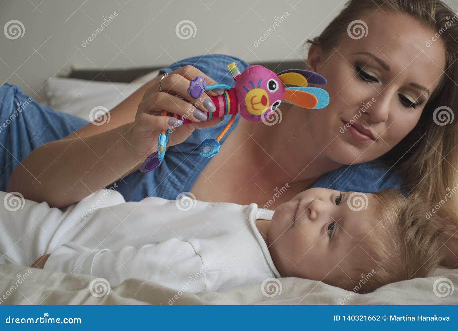 Portrait en gros plan de mère heureuse avec son bébé sur le lit dans la chambre à coucher Jeune maman blonde jouant avec son fils