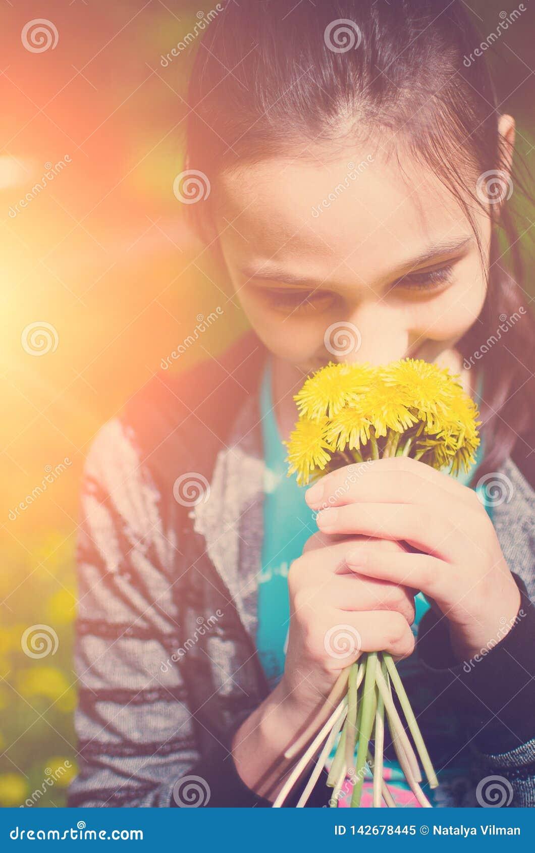 Portrait en gros plan du bouquet de sourire de participation de jeune fille des fleurs dans des mains Fille avec les pissenlits j