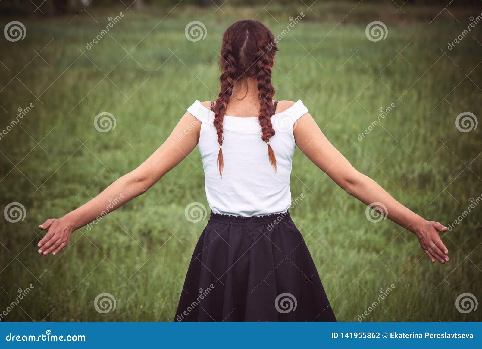 Portrait of enjoying woman raising her hands in the field