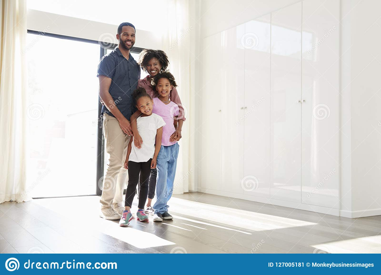 Portrait Of Excited Family Standing In Empty Room Of New Home On Moving Day