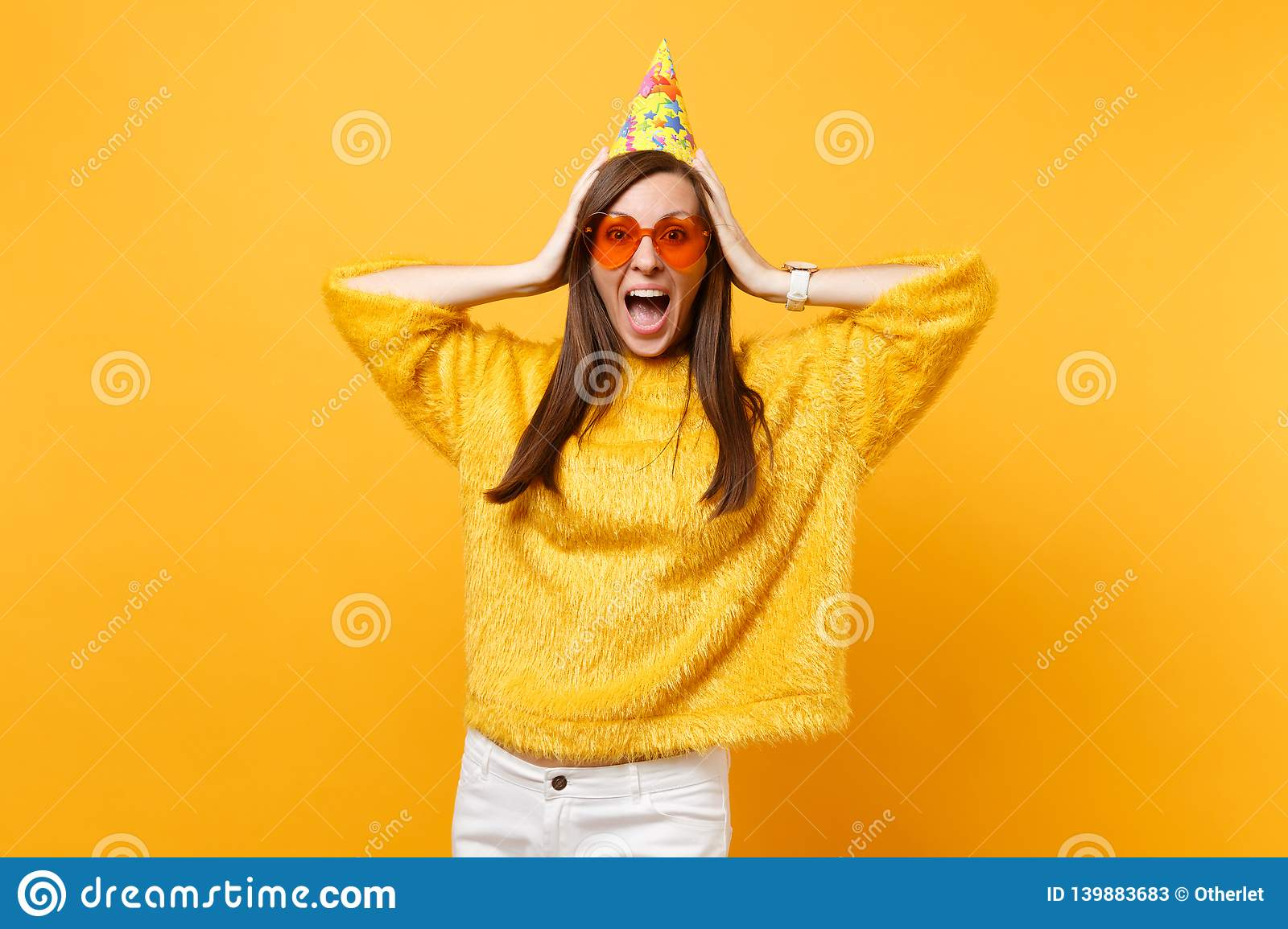 Portrait of excited joyful young woman in orange heart glasses and birthday party hat screaming, putting hands on head