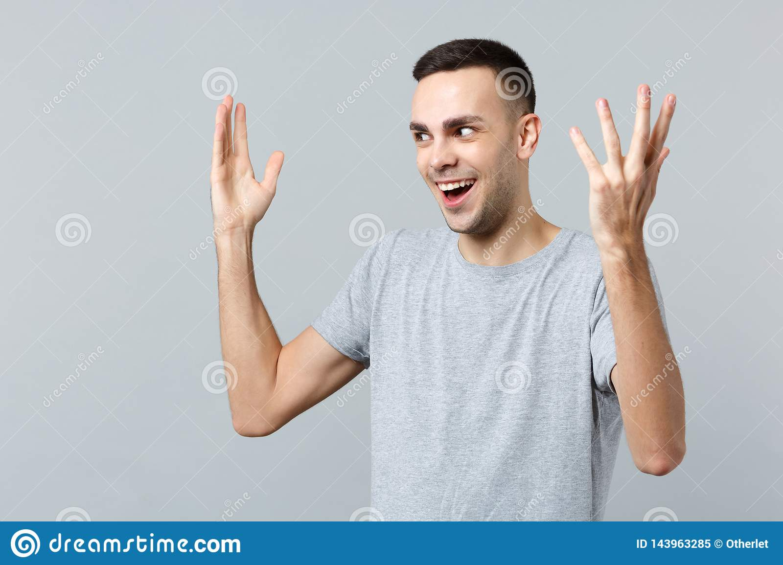Portrait of excited perplexed young man in casual clothes looking aside, rising spreading hands isolated on grey