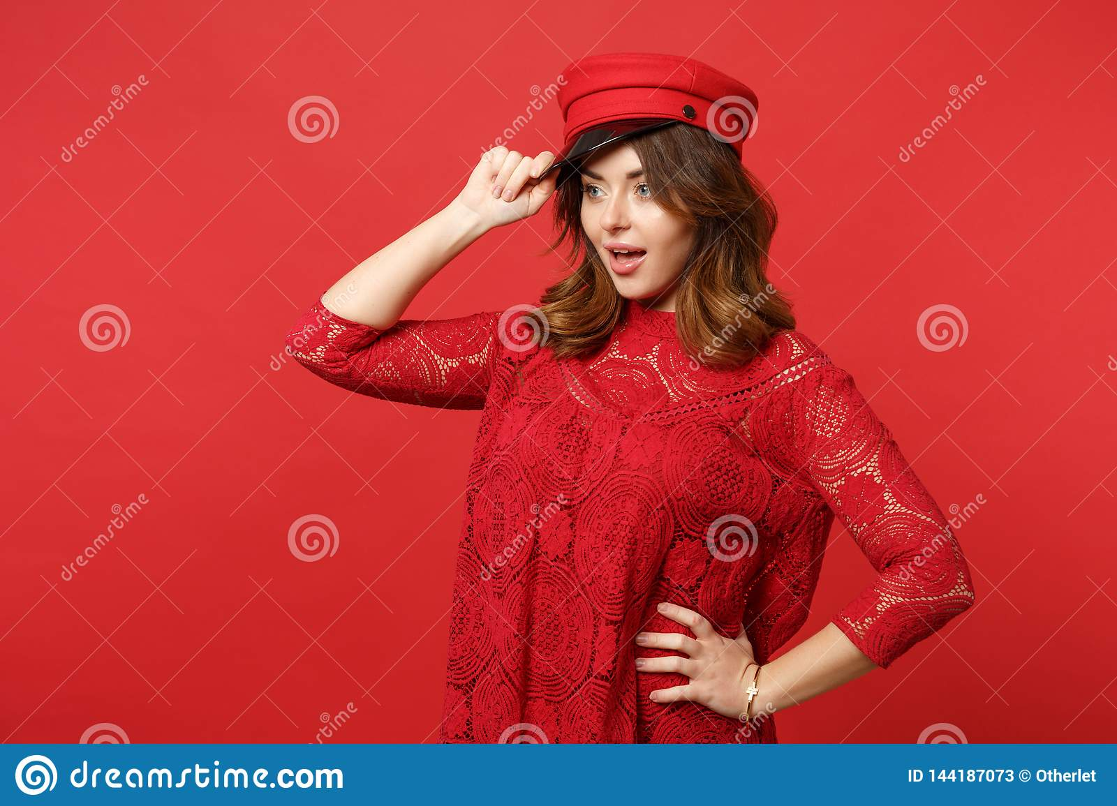 Portrait of excited young woman in lace dress holding cap, keeping mouth open looking aside isolated on bright red