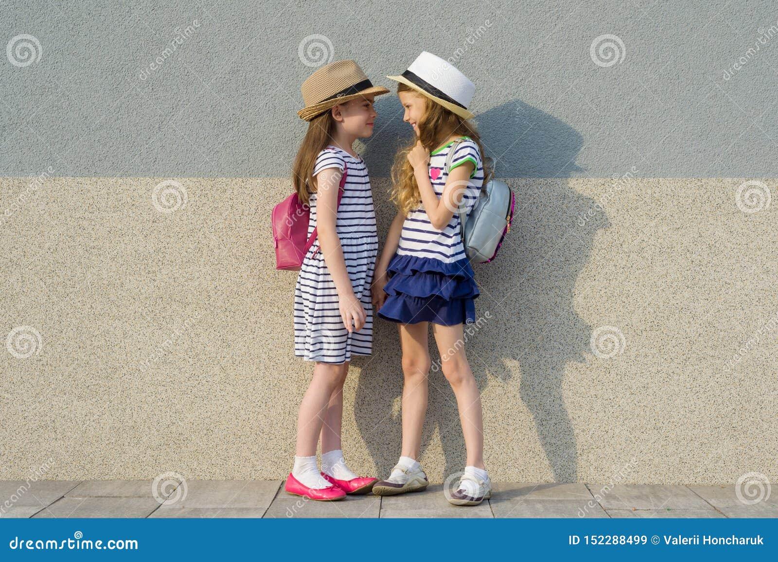 Portrait extérieur d été de deux amie heureux 7,8 ans dans le profil parlant et riant Filles dans des robes rayées, chapeaux avec