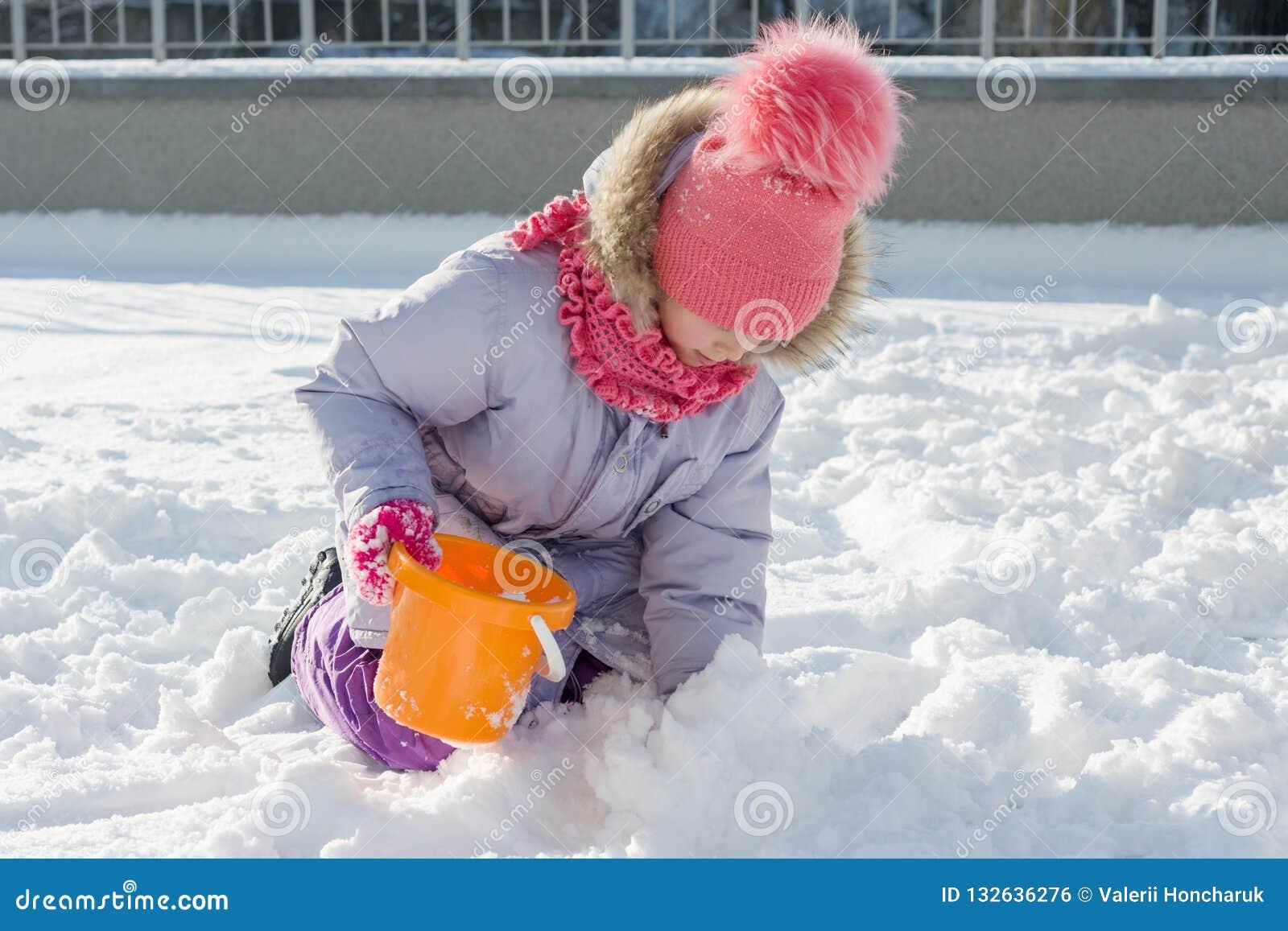 Portrait extérieur d hiver de fille d enfant souriant et jouant avec la neige, jour d hiver ensoleillé lumineux