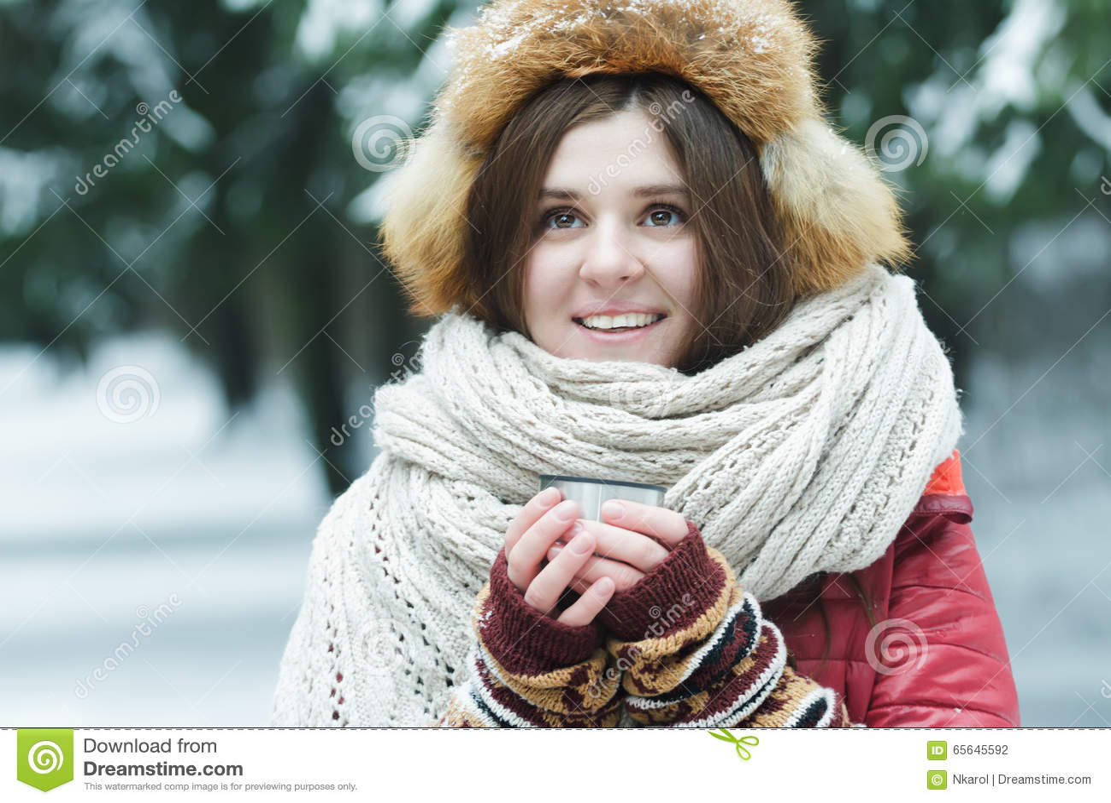 Portrait extérieur d hiver de la jeune dame gaie tenant la tasse de touristes de flacon de vide avec la boisson chaude