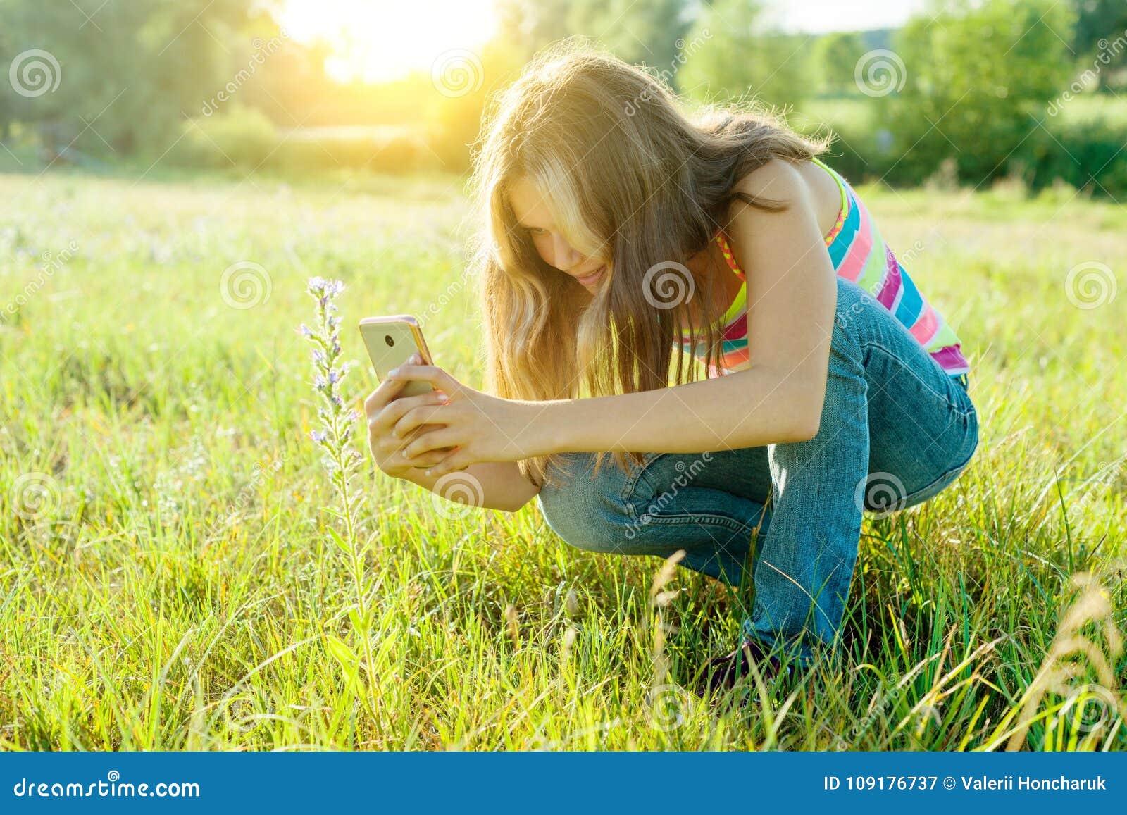 Portrait extérieur d une jeune fille d adolescent à l aide du smartphone pour son blog, et pages dans les réseaux sociaux