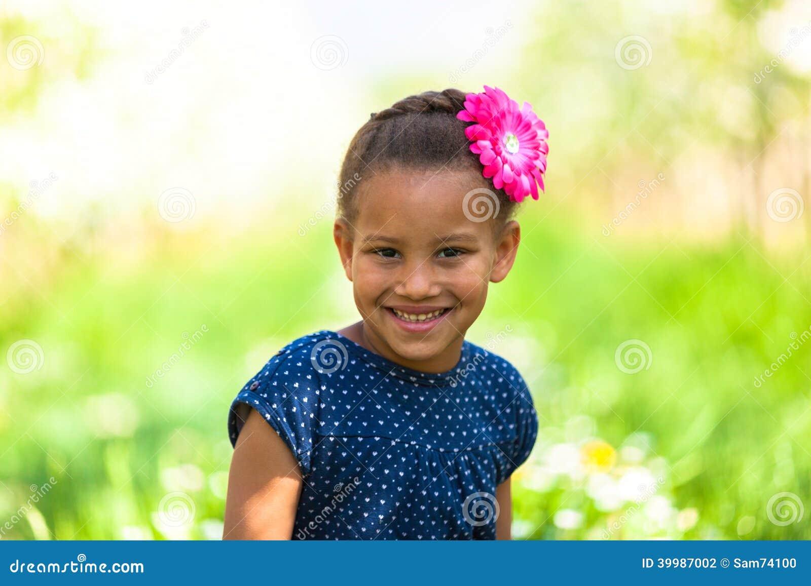 Portrait extérieur d une jeune fille noire mignonne souriant - pe africain
