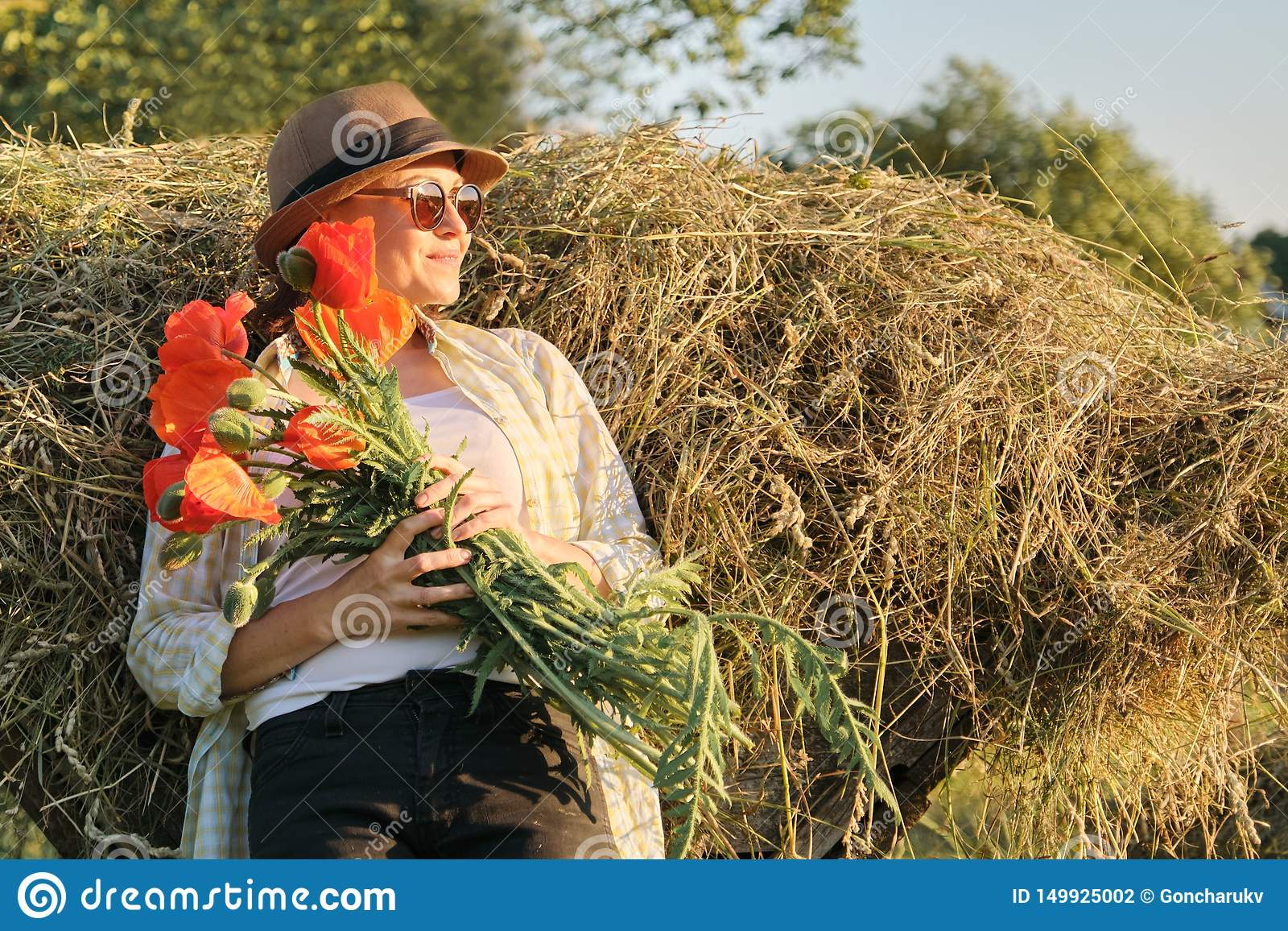 Portrait extérieur de femme mûre heureuse avec un bouquet des fleurs rouges de pavots