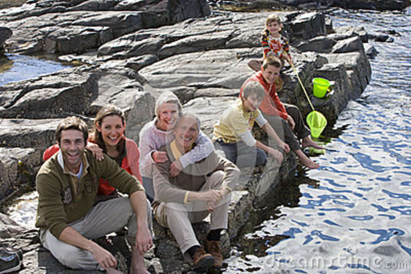 Portrait of family sitting on rock by river