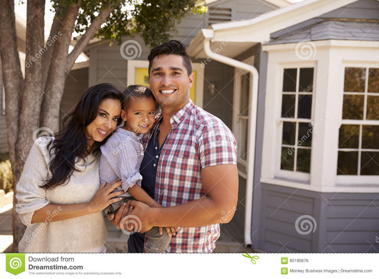Portrait Of Family Standing Outside Home