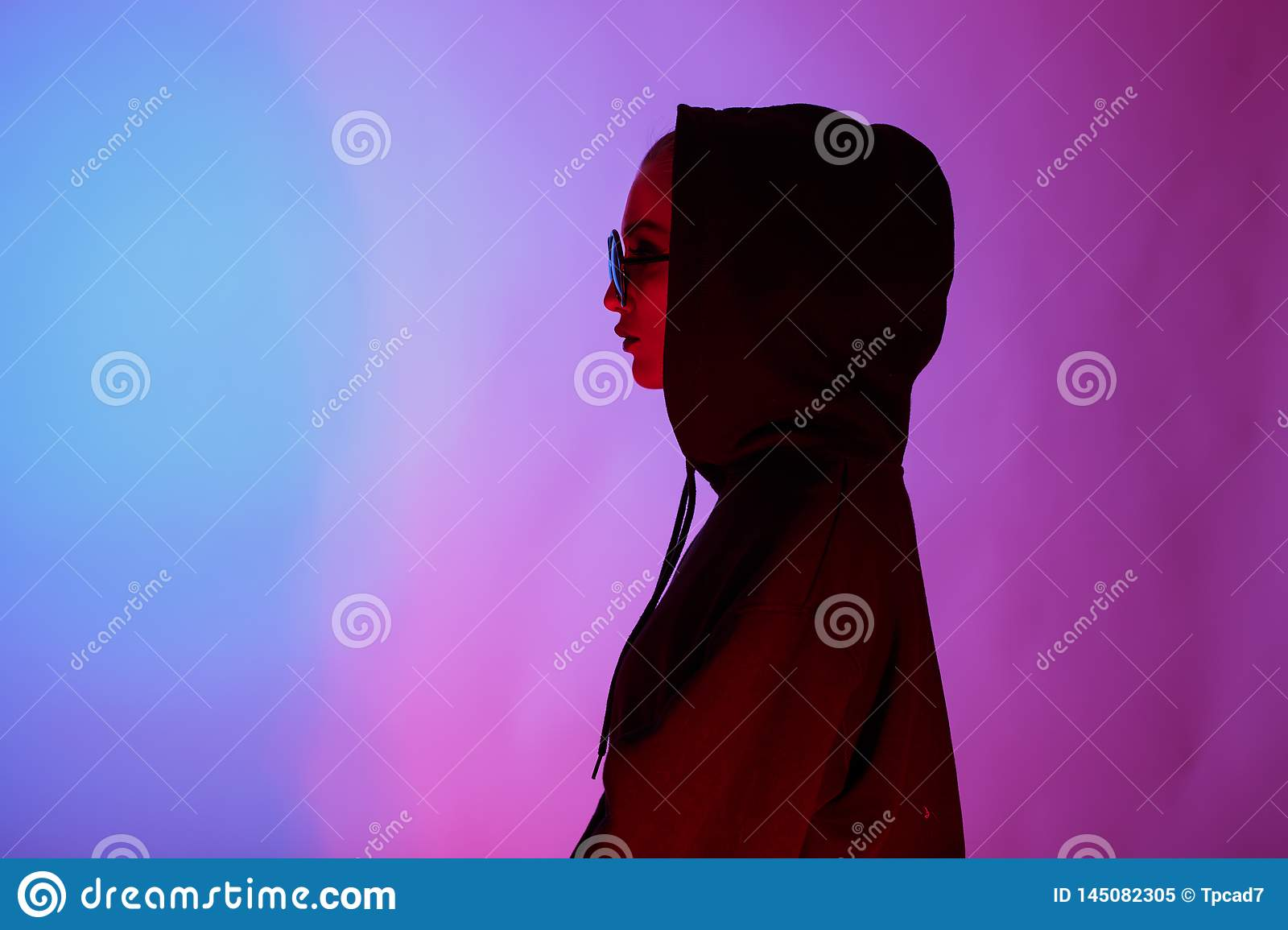 Portrait of fashion young girl in a black sweater with a hood and round sunglasses in red and blue neon light in the