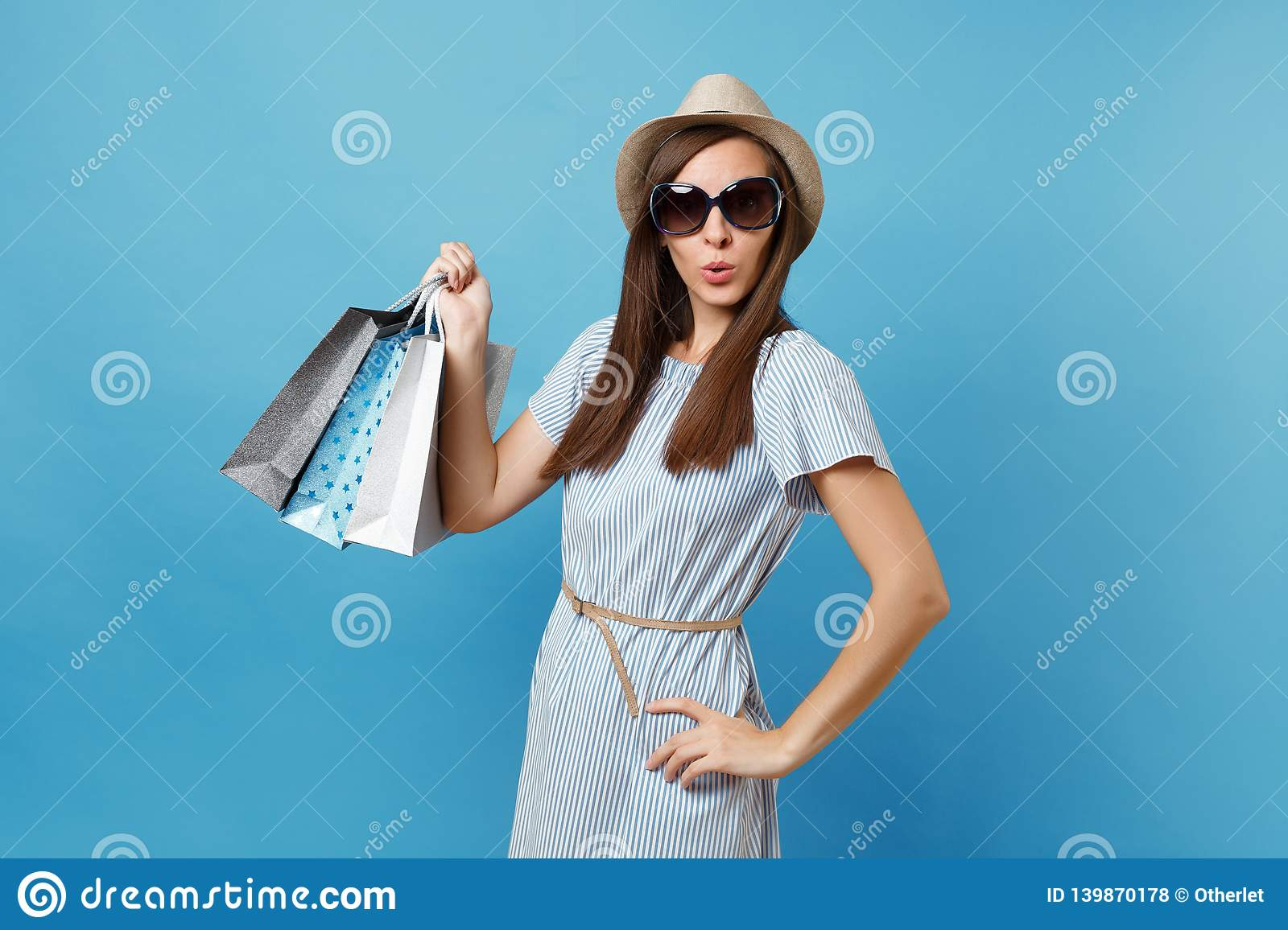 Portrait fashionable attractive happy woman in summer dress, straw hat, sunglasses holding packages bags with purchases