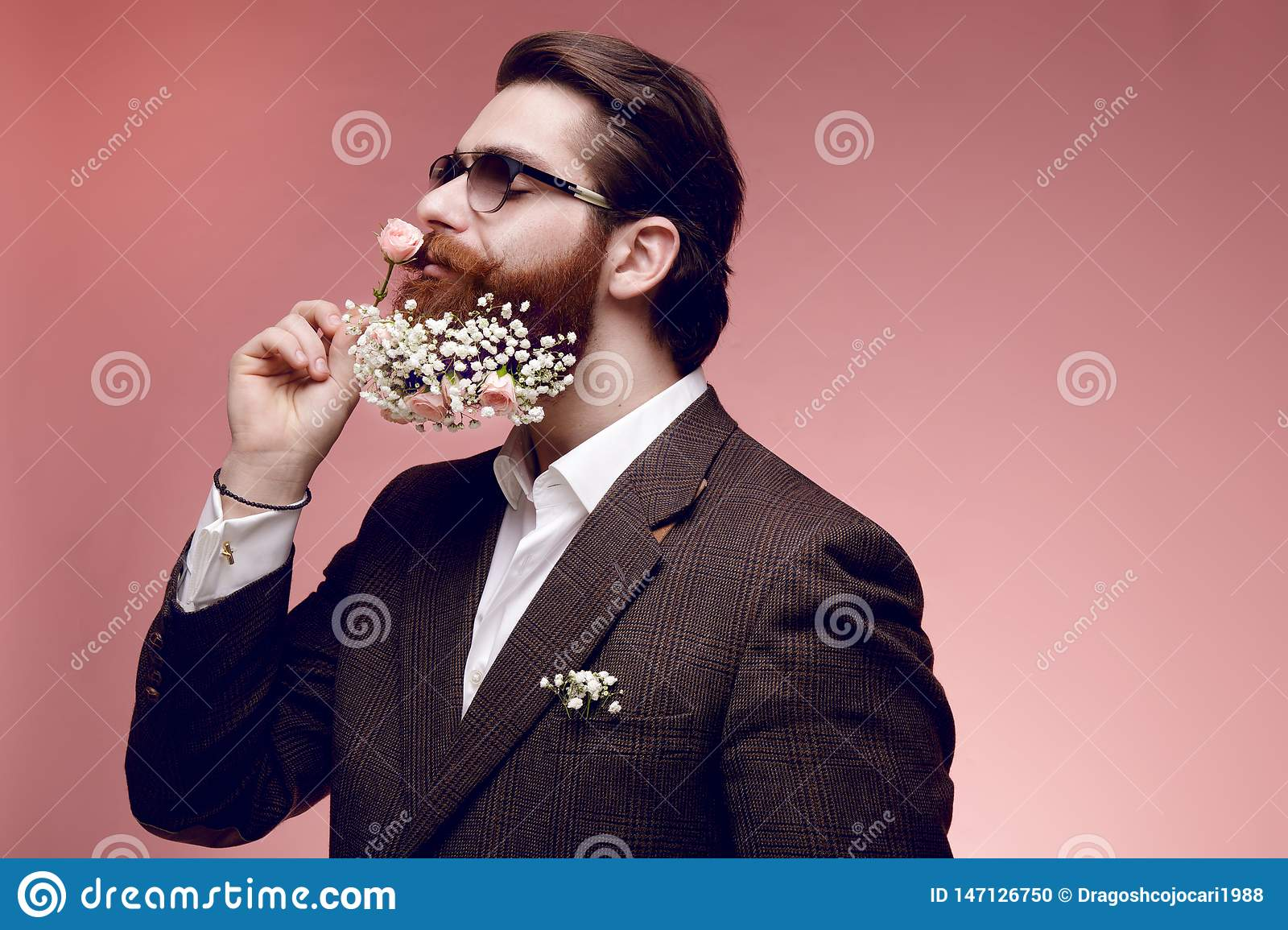 Portrait of a attractive brutal bearded man in sunglasses with flowers in beard, isolated on a dark pink background.