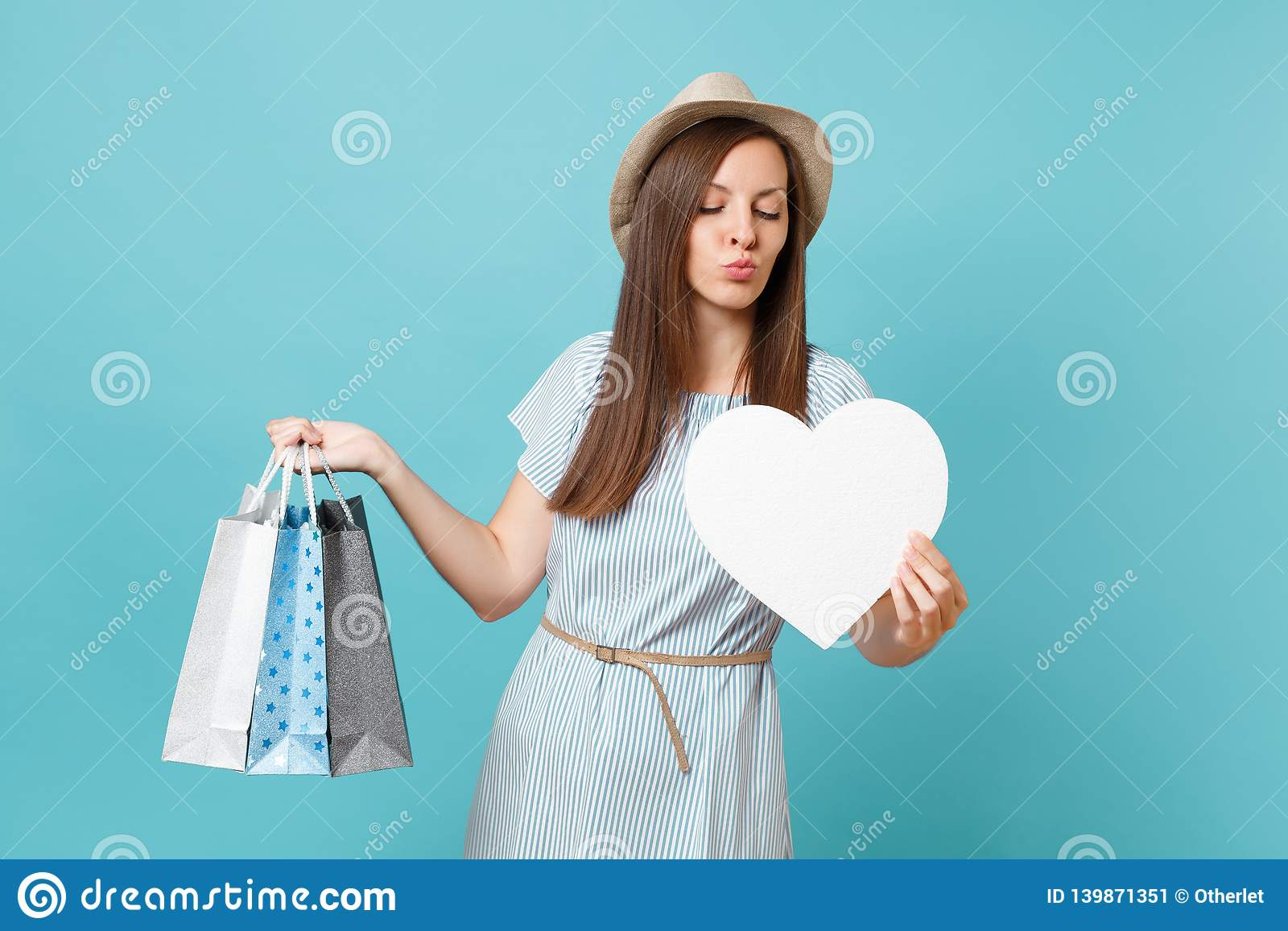 Portrait fashionable beautiful woman in summer dress, straw hat holding packages bags with purchases after shopping