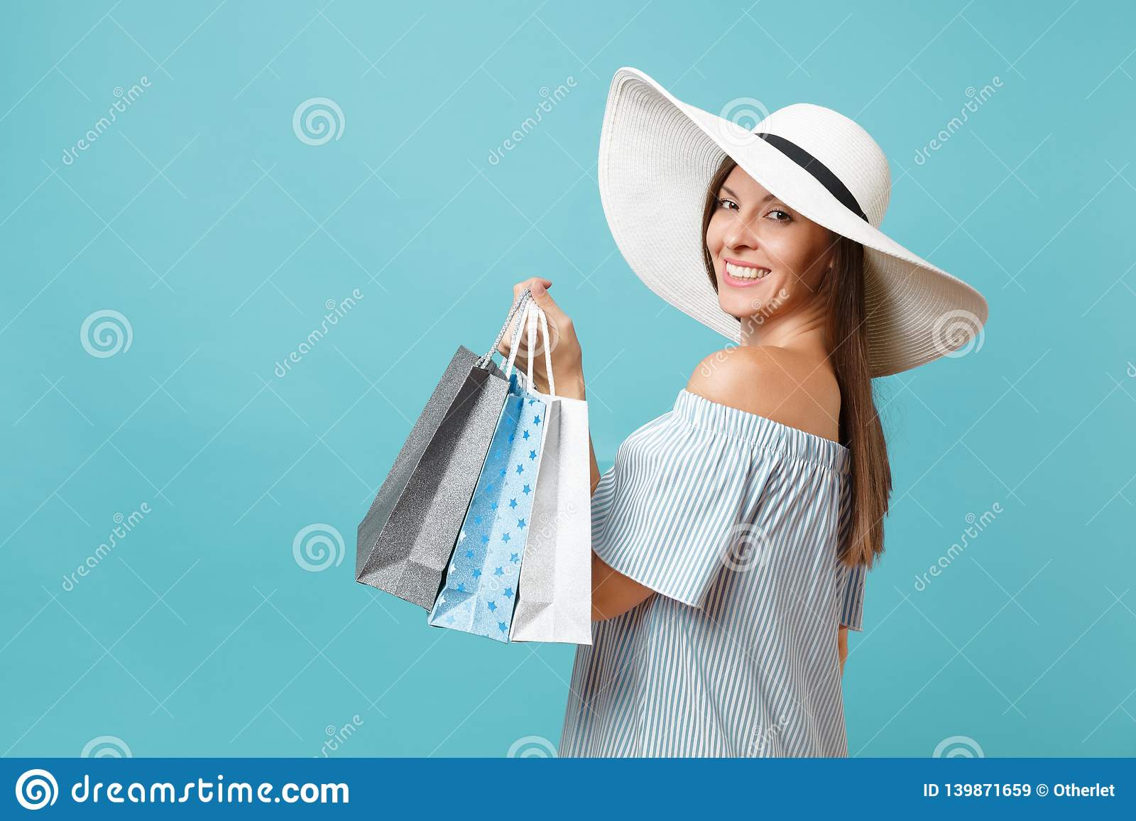 Portrait fashionable elegant fashion beautiful caucasian woman in summer dress, white large wide brim sun hat holding