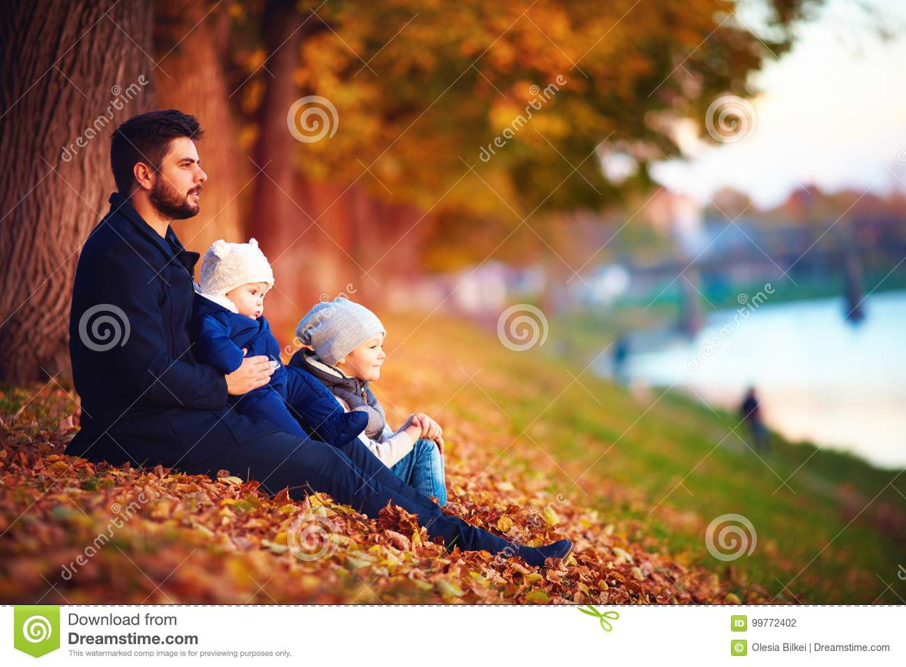 Portrait of father with kids enjoying autumn among fallen leaves