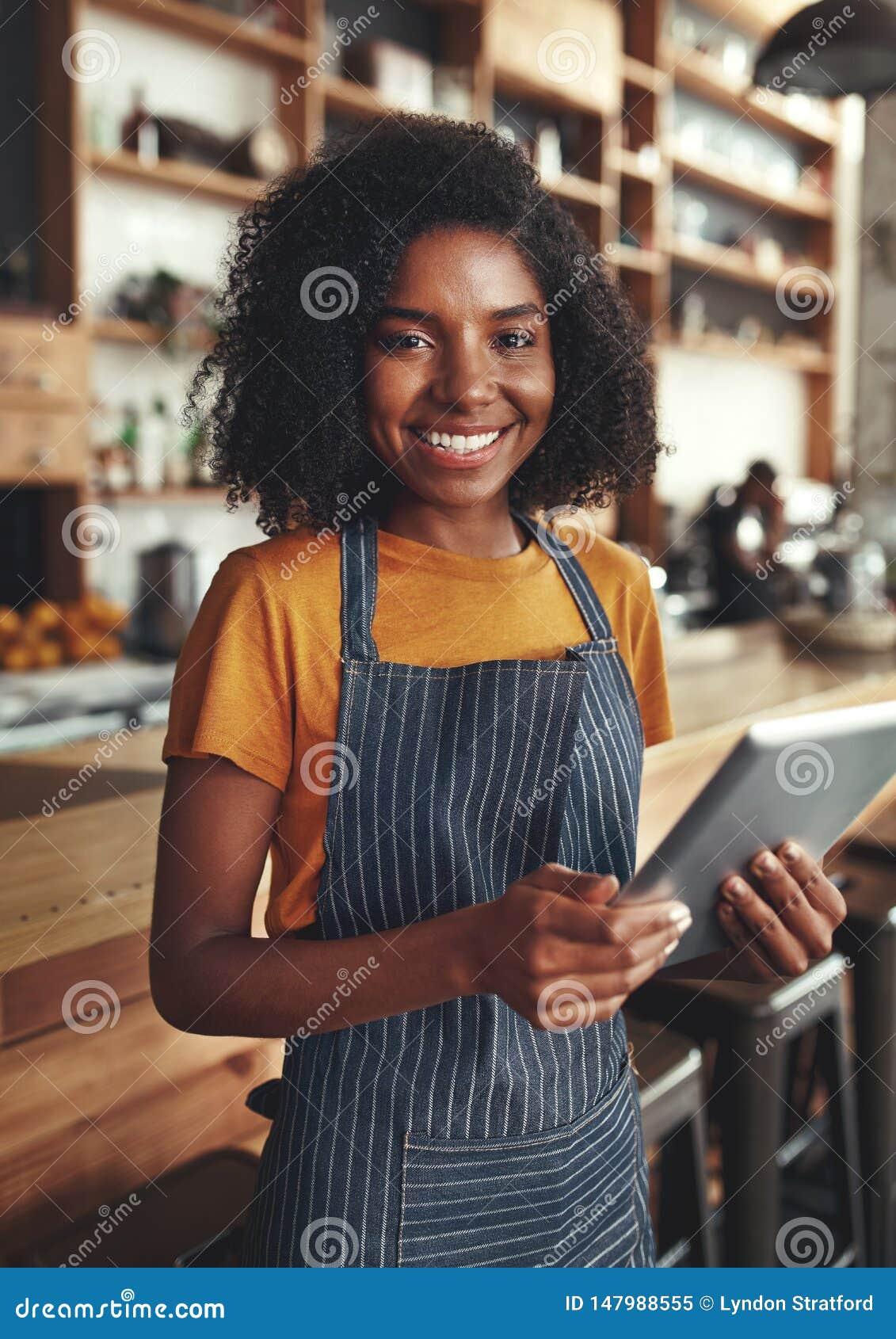 Smiling portrait of a female owner holding digital tablet in her