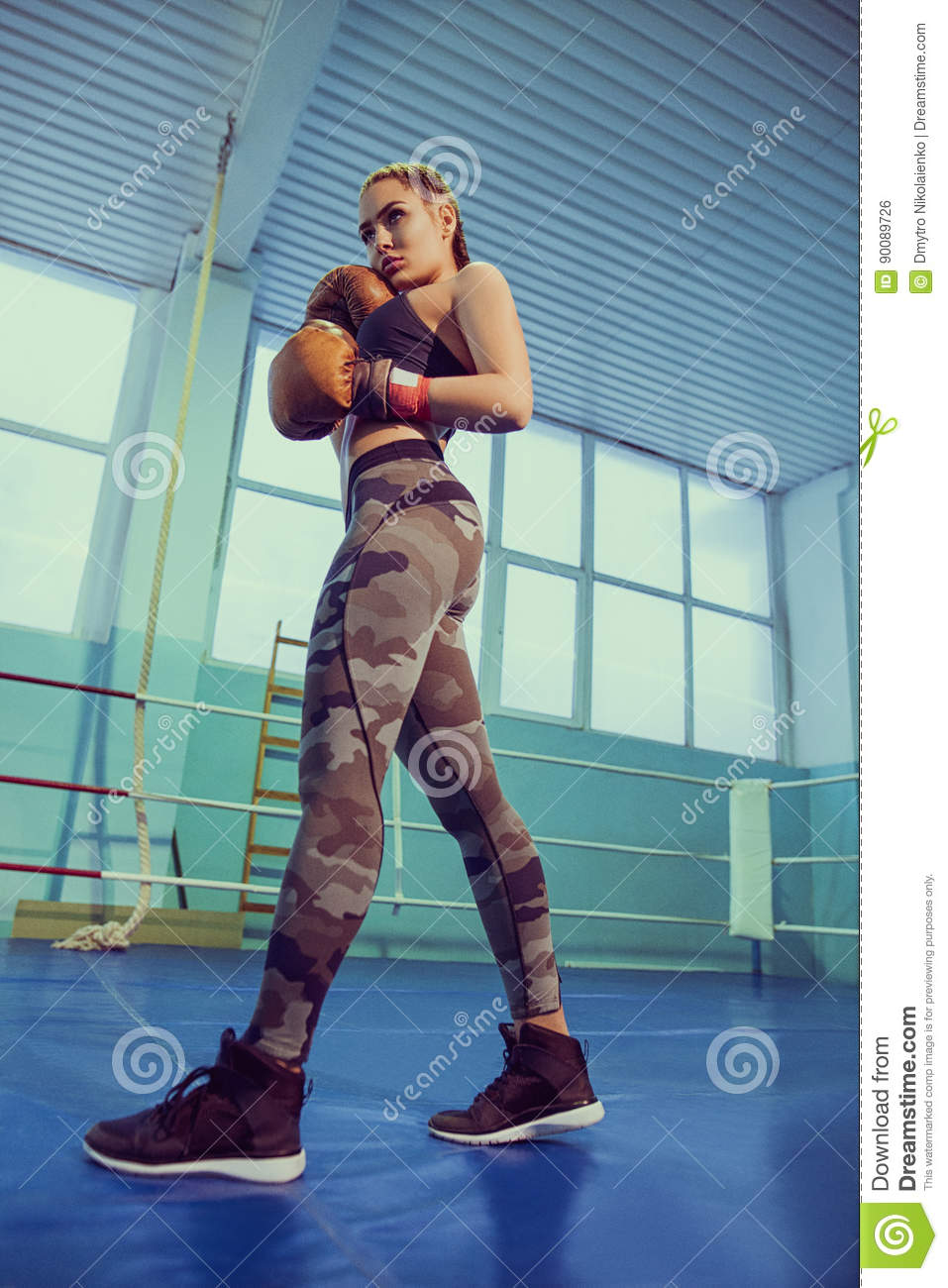 Portrait of female boxer in sport wear with fighting stance against  spotlight. fitness blonde girl in sport wear with perfect body in the  boxing gym posing ...