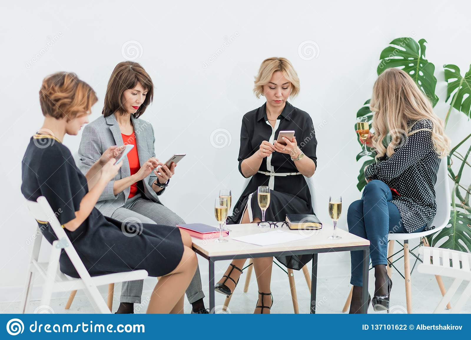Portrait of female business team in modern studio with glasses of champagne.