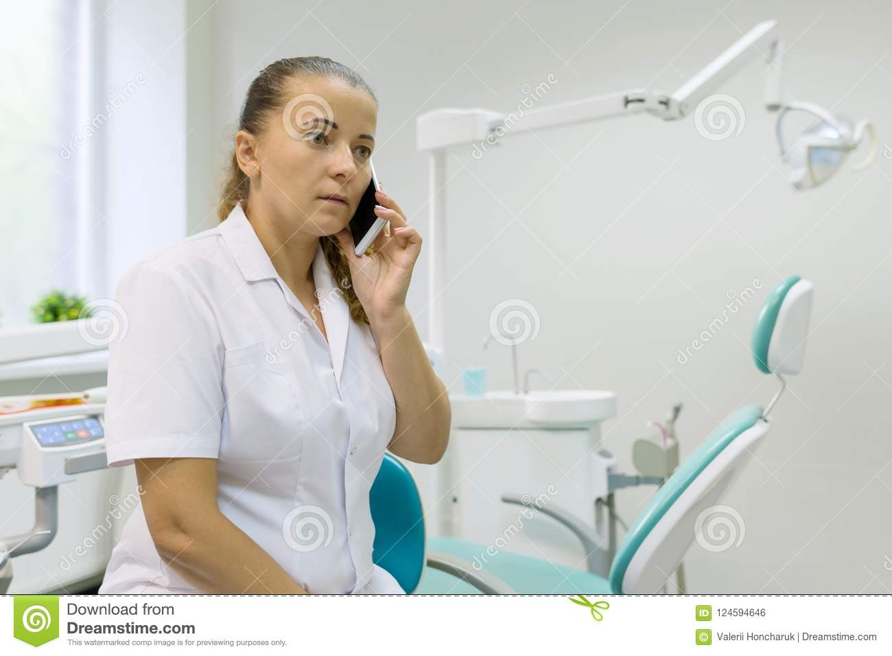 Portrait of a female dentist, doctor talking on mobile phone on dental chair background. Medicine, dentistry and healthcare concep