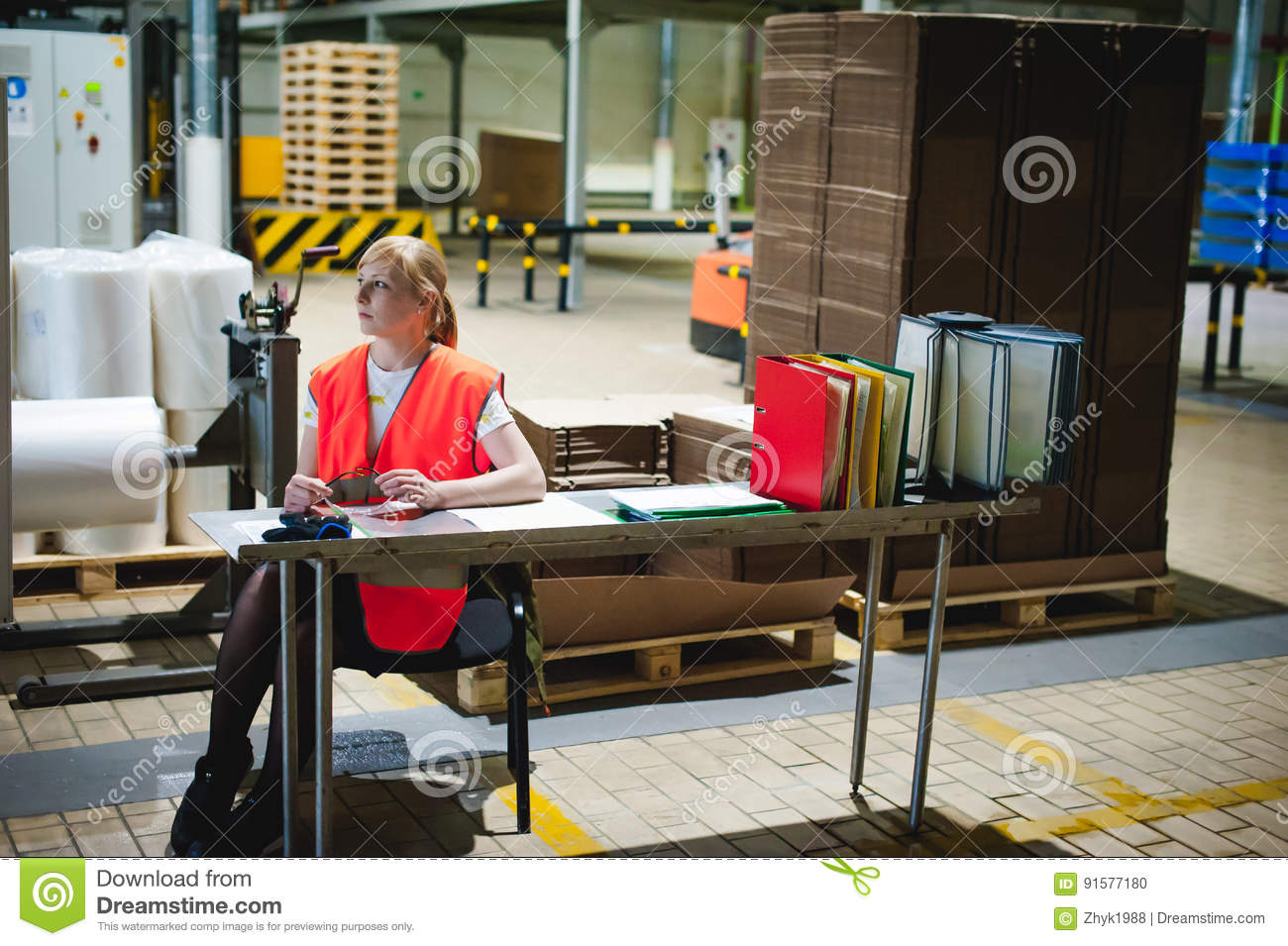 Portrait of a female employee in an orange robe vest in the working space of a production facility, supervises and controls the li