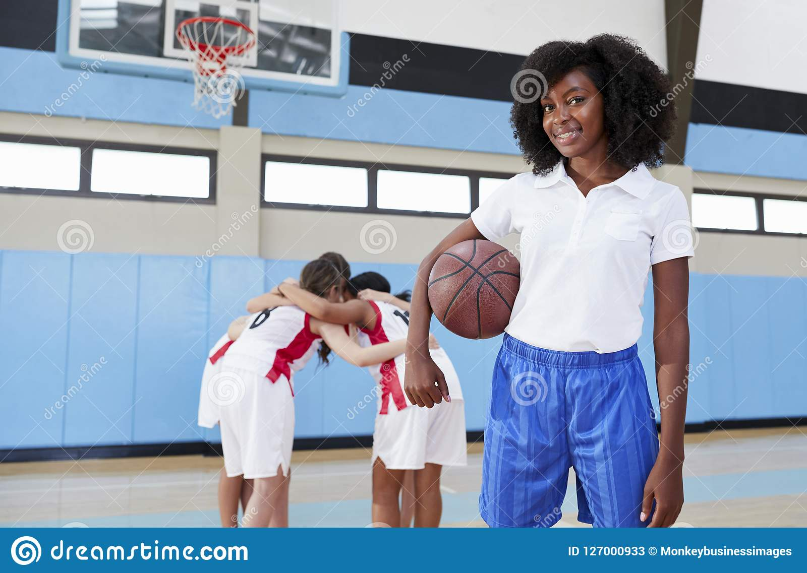 Portrait Of Female High School Basketball Coach With Team Huddle In Background