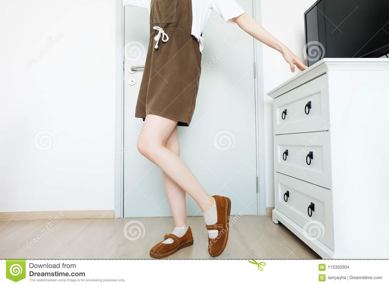 Portrait Female Slim Legs. Girl Long Leg. Beautiful Woman in Brown Dress and Brown Shoes Standing and Posing in The White Roo