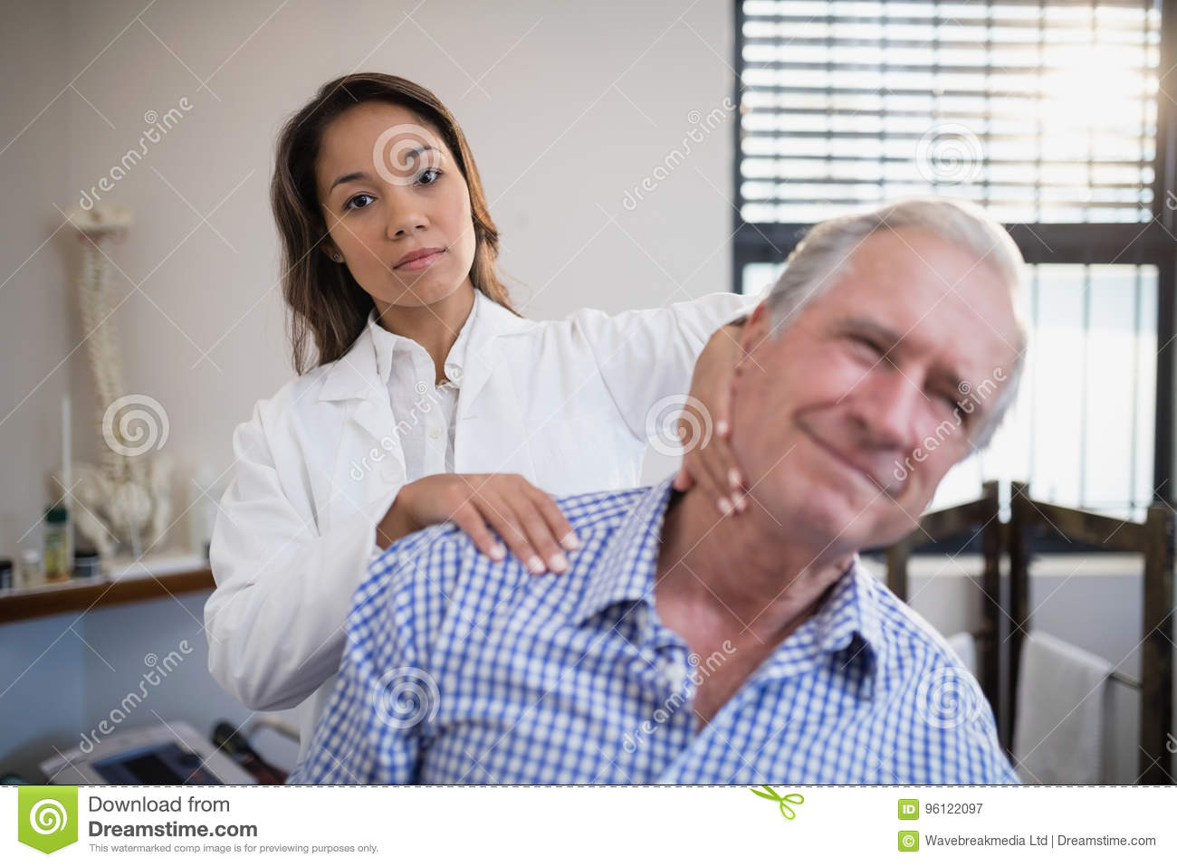 Portrait of female therapist giving neck massage to senior male patient