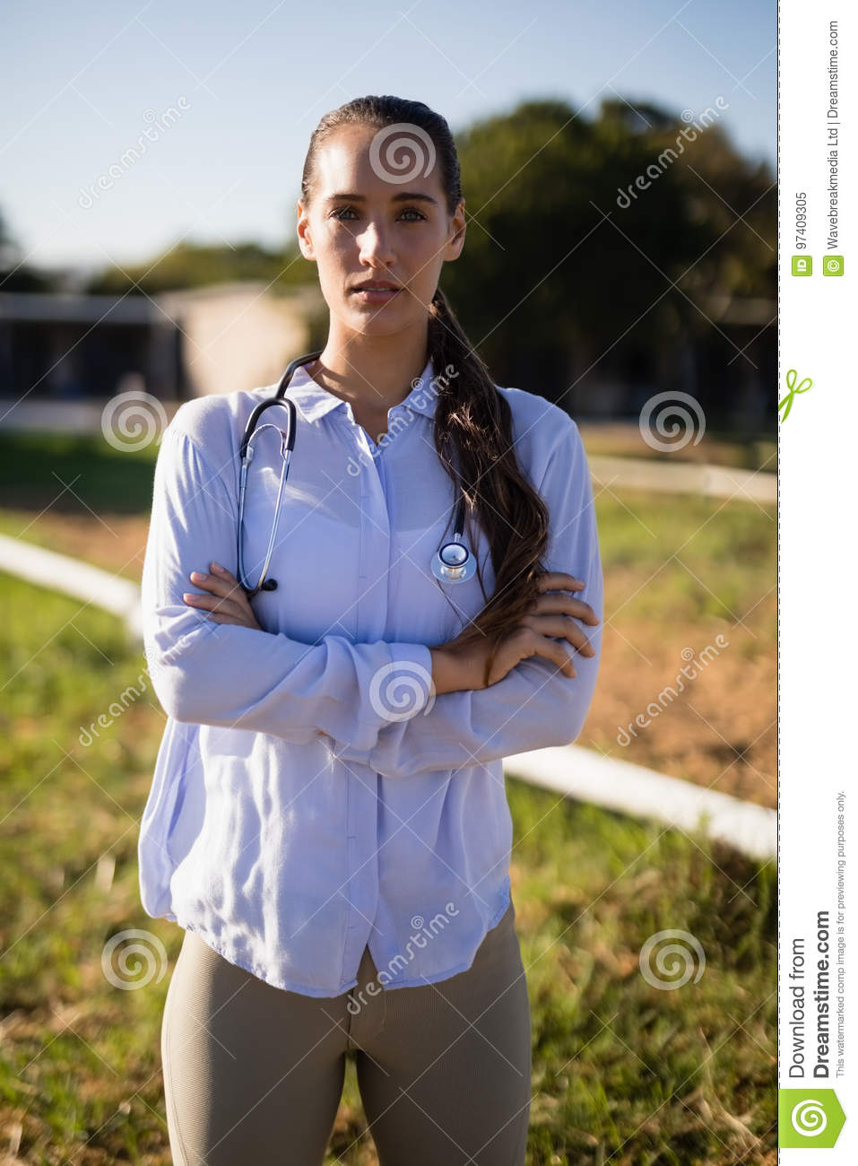 Portrait of female vet with arms crossed standing at barn