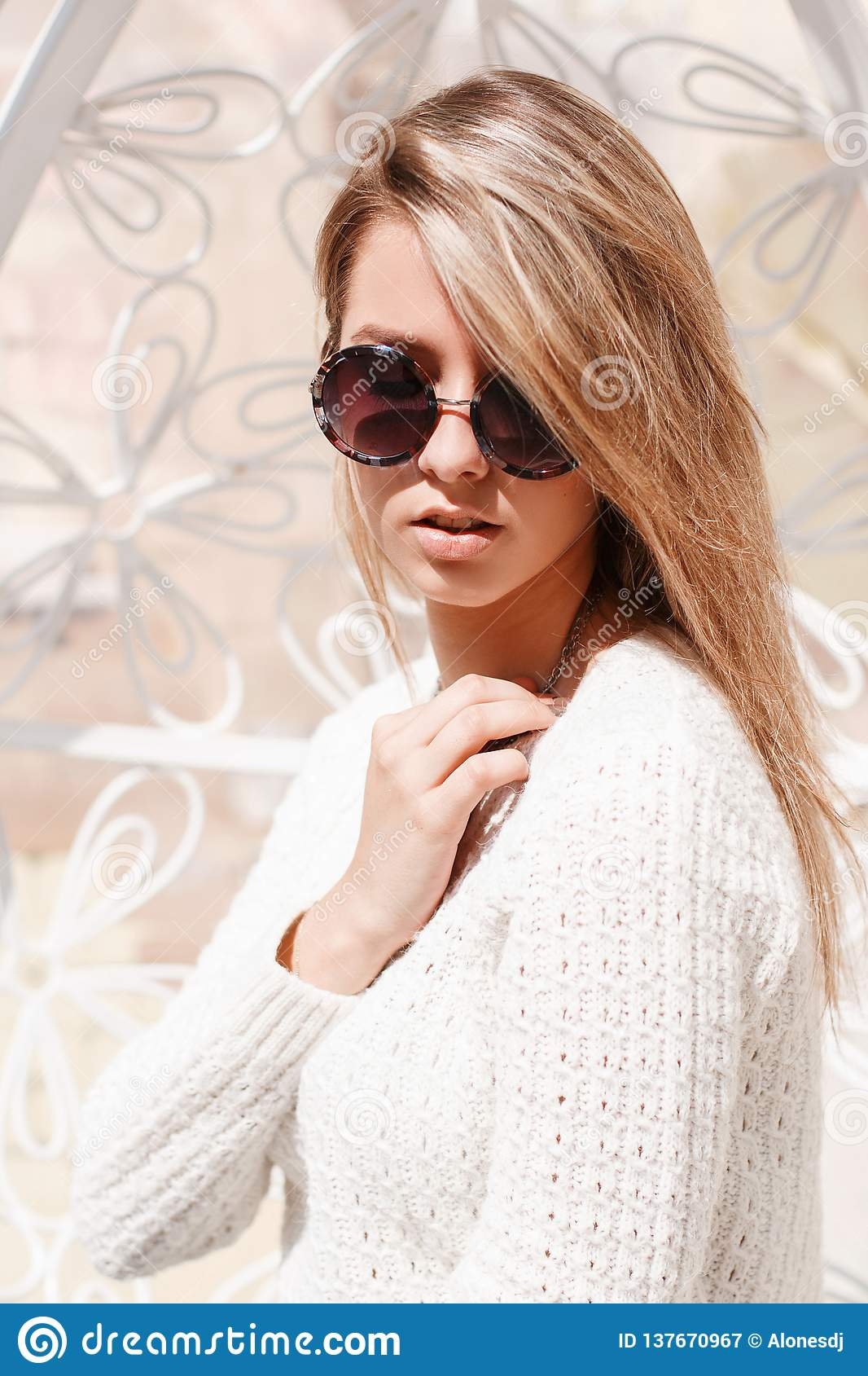 Portrait of a feminine young hipster women in round sunglasses in a knitted white sweater with white hair