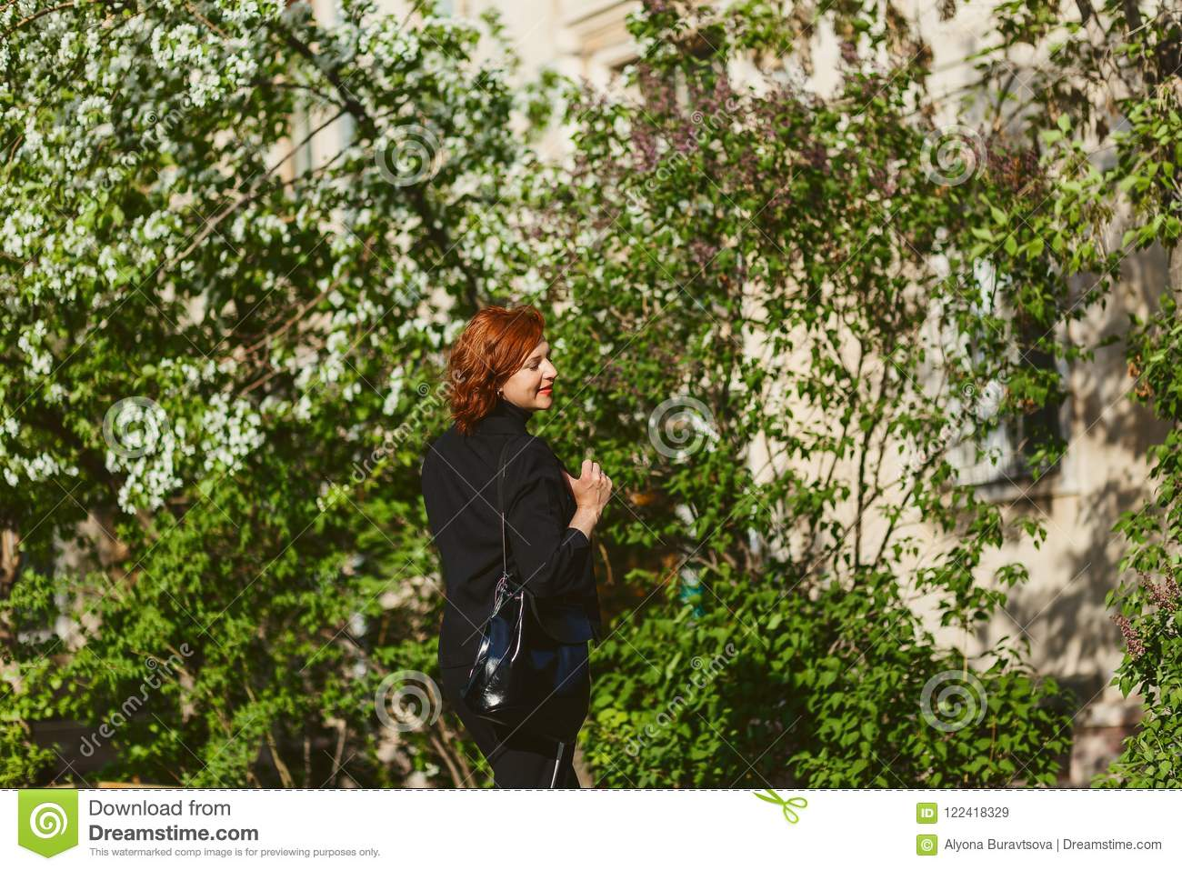Portrait of forty-year-old red-haired woman in profile outdoors in summer