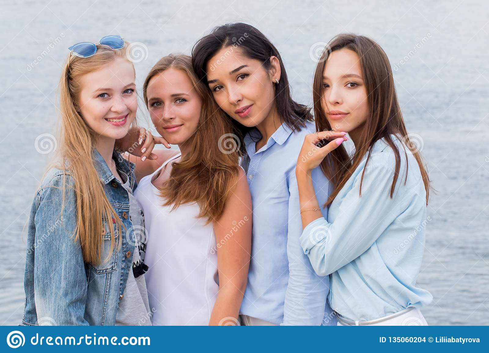 Portrait of four young female friends walking on the sea shore looking at camera laughing