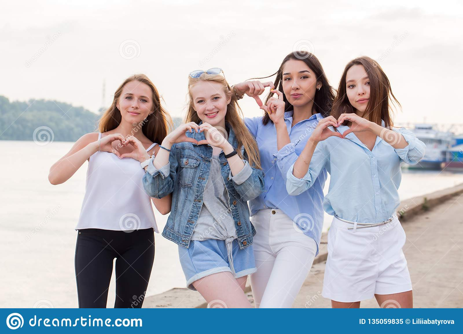 Portrait of four young student girls showing finger gesture heart. Beautiful happy young women on the waterfront