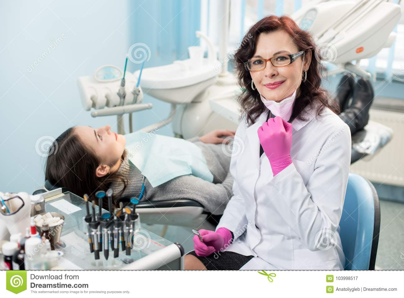 Portrait of friendly female dentist with patient in the chair at the dental office