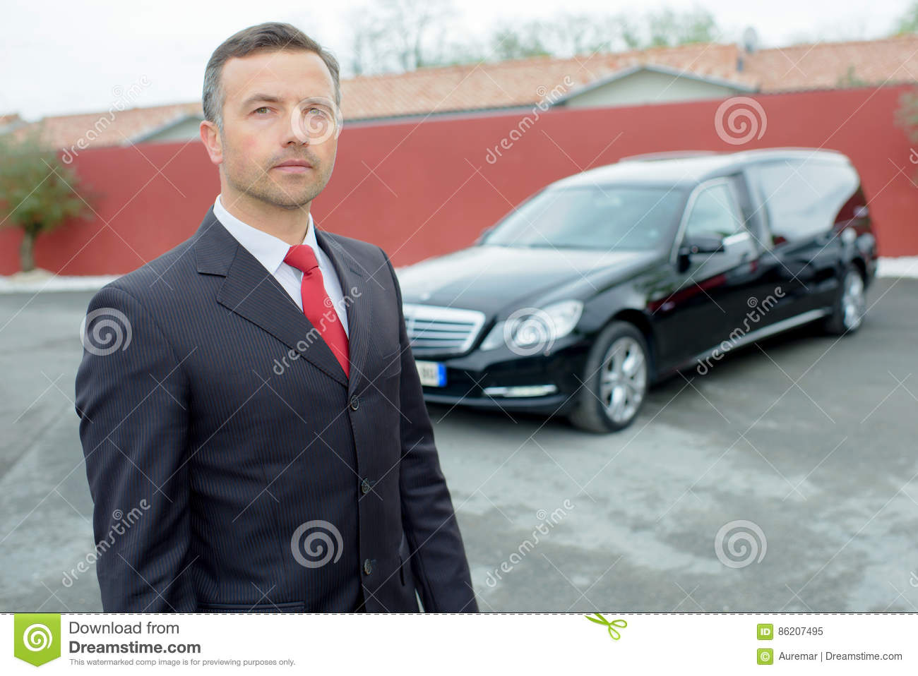 Portrait funeral director in front hearse