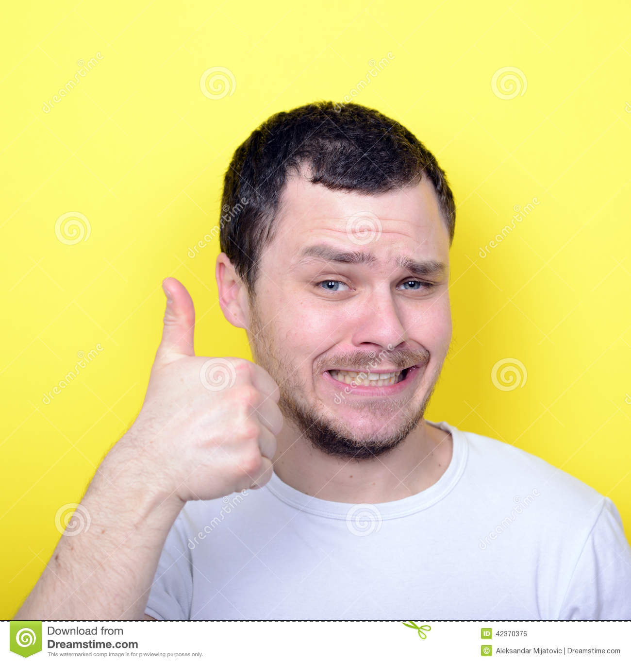 Portrait of with funny expression holding thumbs up against yell