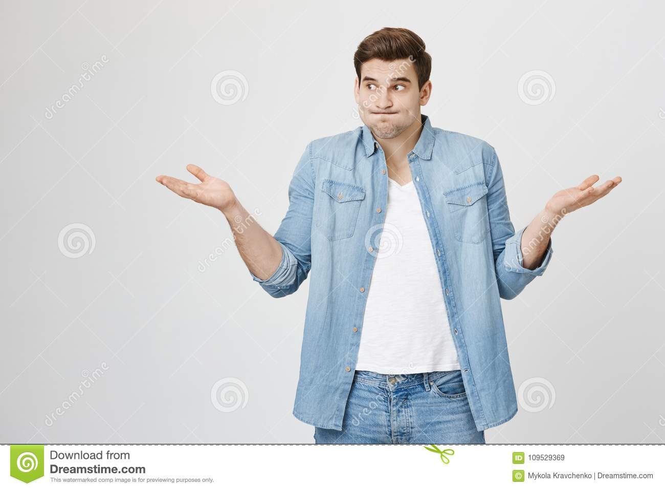 Portrait of funny handsome guy, shrugging and spreading hands, expressing unknowladge and confusion, widen eyes
