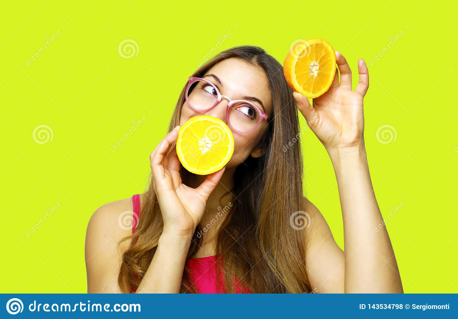 Portrait of funny happy girl holding halves of orange near face