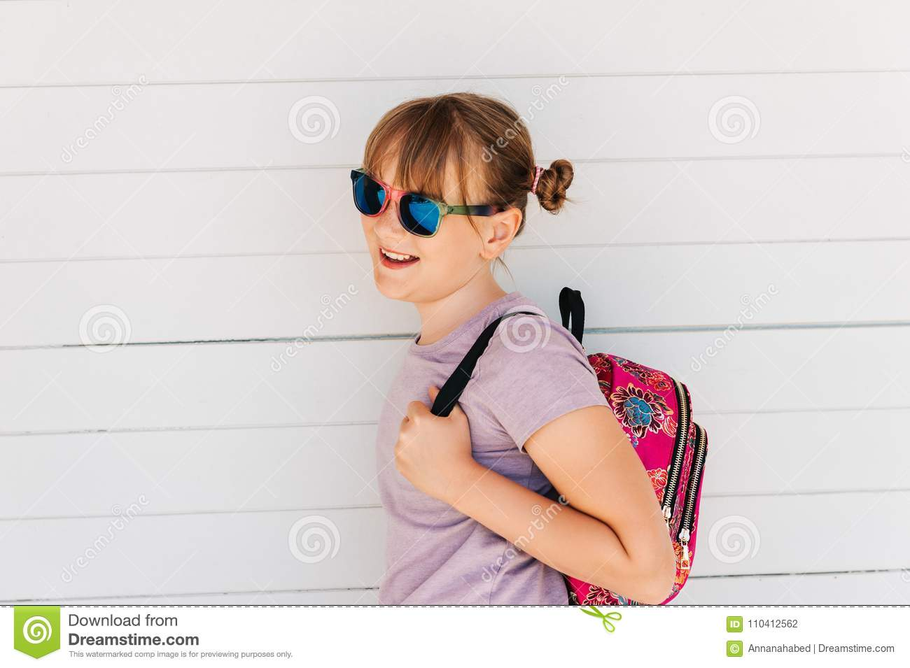 c43a455cae7d Portrait of funny preteen kid girl, wearing sunglasses, holding backpack