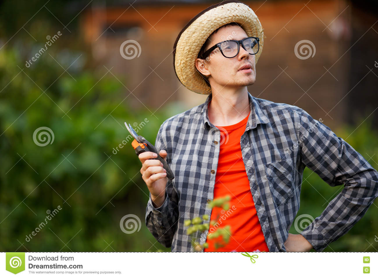 Portrait of gardener young man holding pruning sheers outdoors