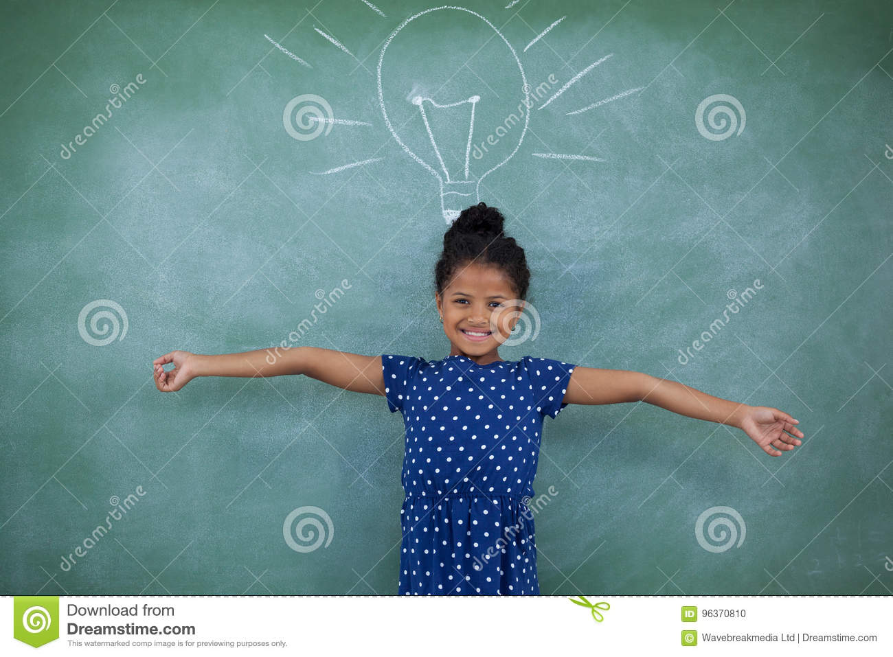 Portrait of girl with arms outstretched by bulb drawing on wall