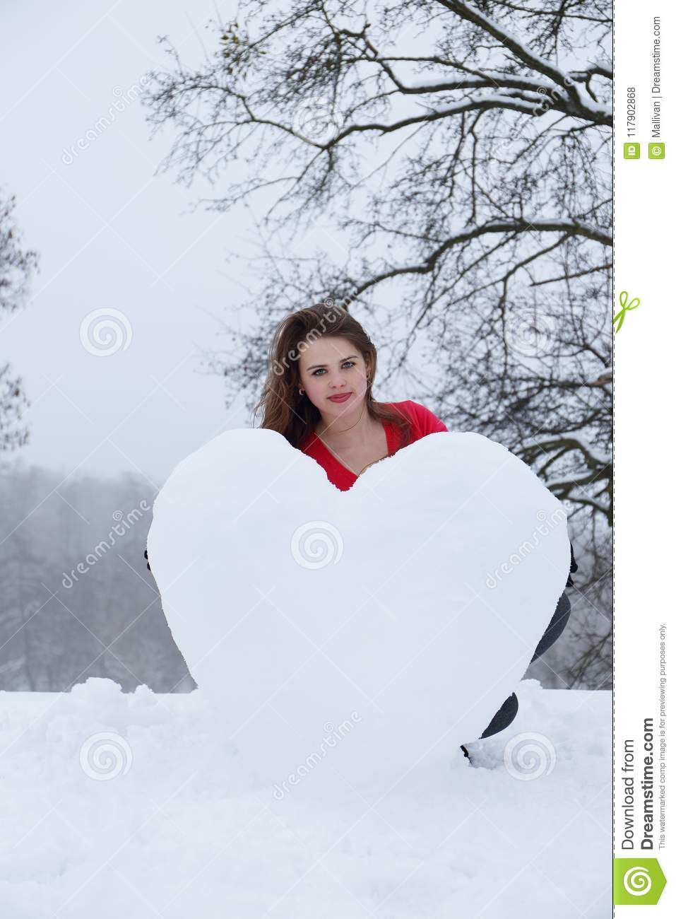 Woman molds a heart of the snow