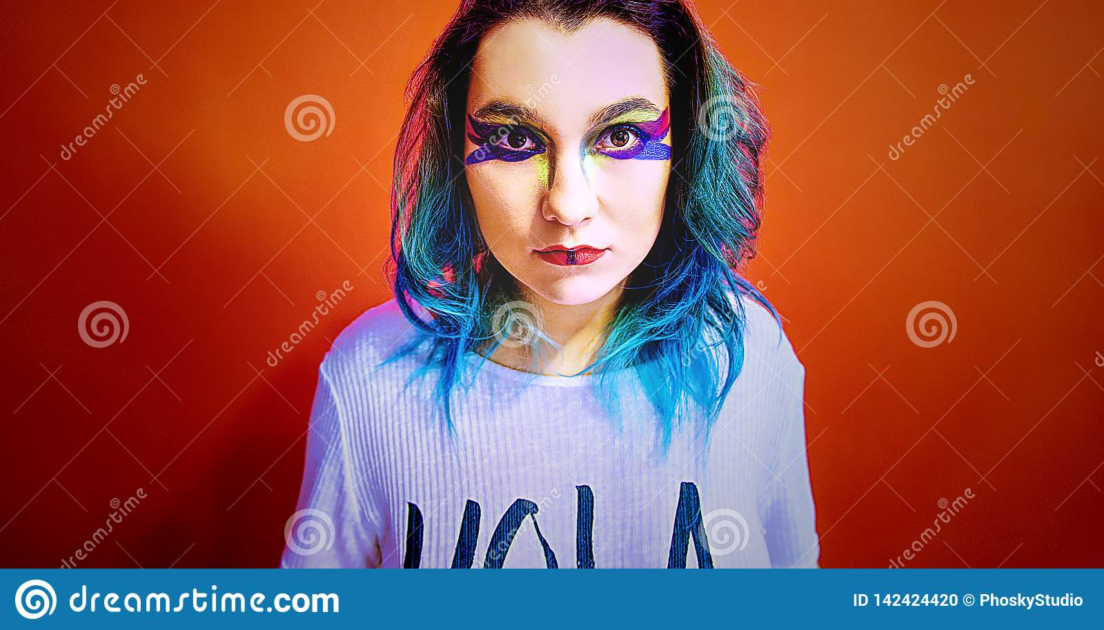 Portrait of a girl with blue hair in a very colorful make-up.