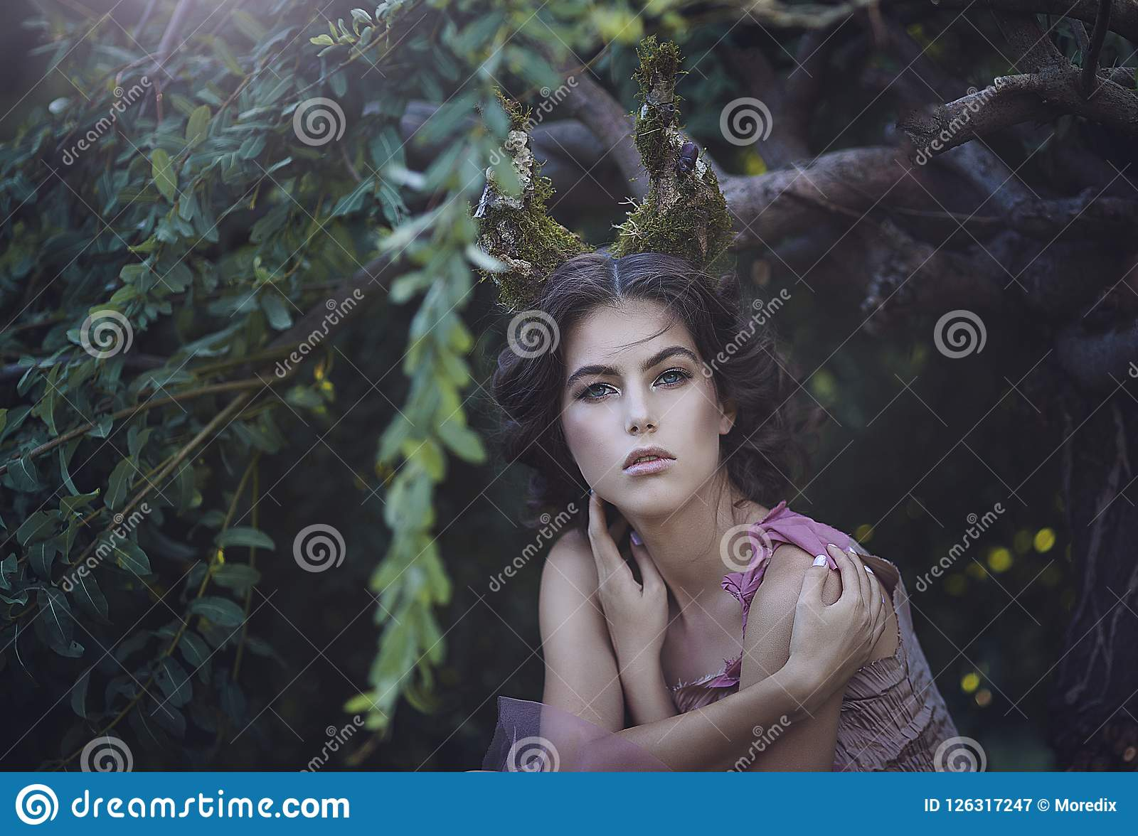 Portrait of girl enchanted Princess with horns. Girl Mystical creature fawn in shabby clothes in a fairy forest