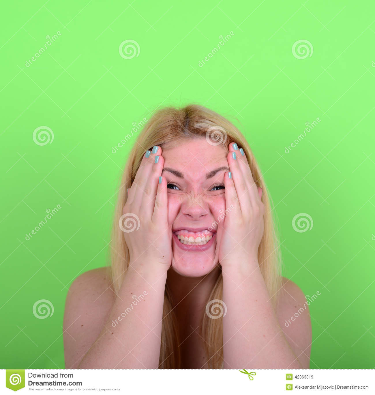 Portrait of girl with funny face against green background