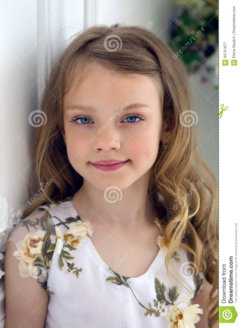 Portrait of a girl seven years old with blond hair and white dress
