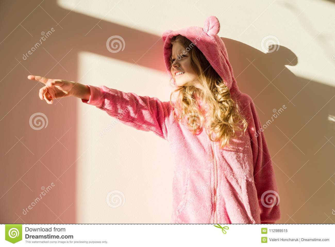 Portrait of a girl in soft warm pink pajamas. Girl 7 years old, blonde with long curly hair, in a hood, looking away.